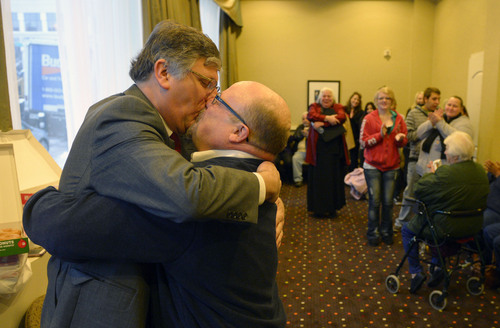 Steve Griffin  |  The Salt Lake Tribune   Gage Church, left, and his husband, Tim Sharp, embrace and kiss they are announced husband and husband Father Robert Trujillo, of Glory To God Old Catholic Church, at the Hampton Inn Suites in Ogden, Utah Monday, December 23, 2013. Volunteer clergy were performing marriage ceremonies for couples across the street from the Weber County Clerk's Office in downtown Ogden.