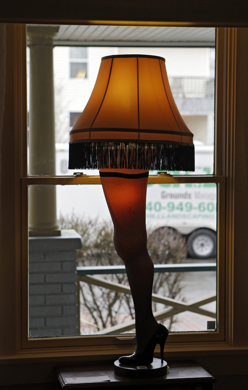 """In this Nov. 21, 2013, photo, a leg lamp is framed in the window of the house in Cleveland where much of the 1983 movie """"A Christmas Story"""" was filmed. A surge of visitors is expected to tour the restored house, and purchase a miniature lamp or two at the gift shop, on the 30th anniversary of the quirky holiday film. (AP Photo/Mark Duncan)"""