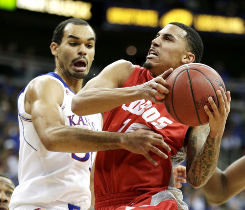Kansas' Perry Ellis, left, pressures New Mexico's Kendall Williams during the second half of an NCAA college basketball game Saturday, Dec. 14, 2013, in Kansas City, Mo. Kansas won the game 80-63. (AP Photo/Charlie Riedel)