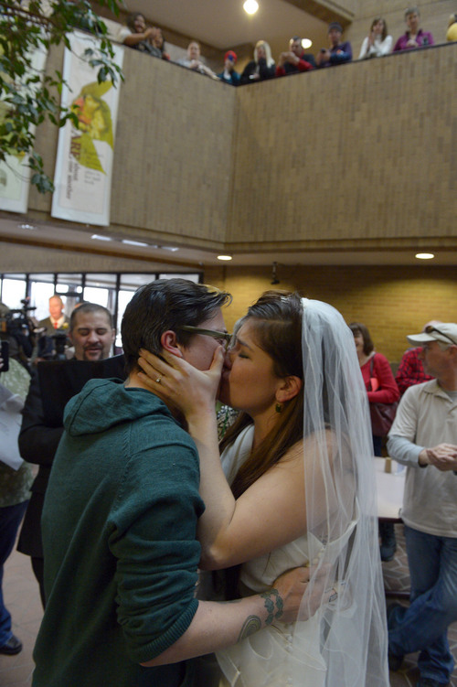 Francisco Kjolseth  |  The Salt Lake Tribune Jax Collins, left, and Heather Collins embrace in a kiss after being married by Rev. Christopher Scuderi of Universal Heart Ministry on Monday, Dec. 23, 2013, at the Salt Lake City County offices. Hundreds of same-sex couples descended on county clerk offices around the state of Utah to request marriage licenses. A federal judge in Utah struck down the state's ban on same-sex marriage last Friday, saying the law violates the U.S. Constitution's guarantees of equal protection and due process.