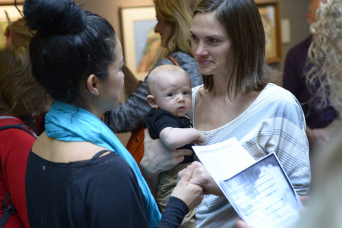 Francisco Kjolseth  |  The Salt Lake Tribune Danielle Torres, left, embraces her partner of 7-years,  Jody Jones holding their son Franti Torres-Jones, 3-months, as they are married in the lobby of the Salt Lake County offices on Monday, Dec. 23, 2013. Hundreds of same-sex couples descended on county clerk offices to request marriage licenses. A federal judge in Utah struck down the state's ban on same-sex marriage last Friday, saying the law violates the U.S. Constitution's guarantees of equal protection and due process.
