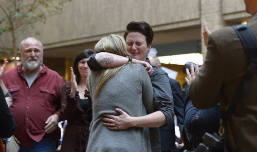Francisco Kjolseth  |  The Salt Lake Tribune Jamie Stocks is overcome with emotion as she embraces her wife Jessica Hamilton after being married in the lobby of the Salt Lake County offices on Monday, Dec. 23, 2013. Hundreds of same-sex couples descended Salt Lake County offices to request marriage licenses. A federal judge in Utah struck down the state's ban on same-sex marriage last Friday, saying the law violates the U.S. Constitution's guarantees of equal protection and due process.