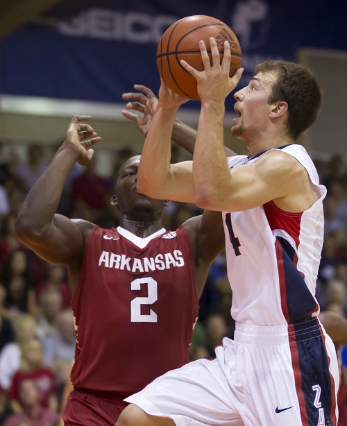 Gonzaga guard Kevin Pangos, right, looks for his shot at the basket while being defended by Arkansas forward Alandise Harris (2) in the first half of an NCAA college basketball game at the Maui Invitational on Wednesday, Nov. 27, 2013, in Lahaina, Hawaii. (AP Photo/Eugene Tanner)