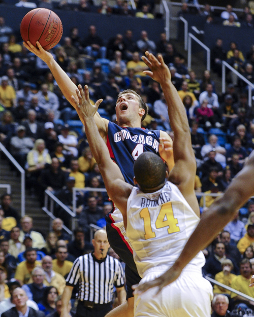 Gonzaga's Kevin Pangos, top, shoots over West Virginia's Gary Browne (14) during the first half of an NCAA college basketball game Tuesday, Dec. 10, 2013, in Morgantown, W.Va. (AP Photo/Andrew Ferguson)