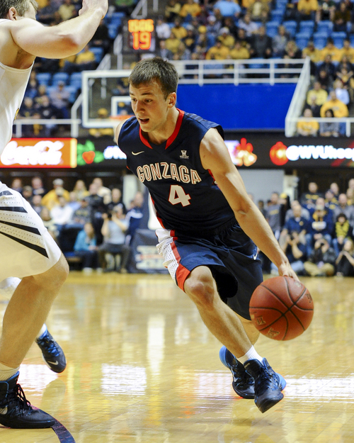 Gonzaga's Kevin Pangos (4) drives past a West Virginia defender during the first half of an NCAA college basketball game Tuesday, Dec. 10, 2013, in Morgantown, W.Va. (AP Photo/Andrew Ferguson)