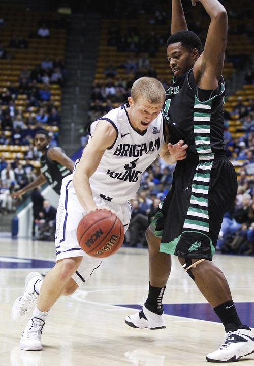 BYU's Tyler Haws drives past UNT's T.J. Taylor, right, during the NCAA men's basketball game between BYU and University of North Texas at the Marriott Center in Provo on Tuesday, Dec. 3, 2013. BYU won the game 97-67. SPENSER HEAPS