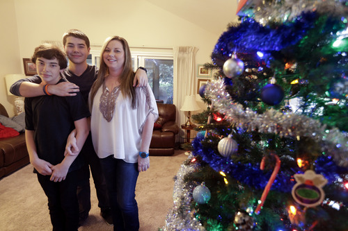 In this Dec. 17, 2013 image, Matthew Kremis, center, poses for a picture with his brother Trevin Kremis, left, and their mother, Deanna Kremis, in their home in San Marcos, Calif. All three have received heart transplants, after suffering with an inherited heart condition. (AP Photo/Gregory Bull)