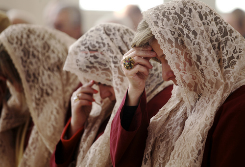 The women of Saint Afram Syrian Orthodox church's choir pray during morning Christmas mass in Amman, Jordan, Wednesday, Dec. 25, 2013. Syrian and Iraqi Orthodox Christian families prayed for peace in their countries. (AP Photo/Mohammad Hannon)