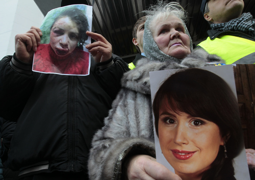 Activists hold the photos of journalist and activist Tetyana Chernovil as they rally outside the Ukrainian Interior Ministry in Kiev, Ukraine, Wednesday, Dec. 25, 2013. Tensions escalated further on Wednesday when a journalist and opposition activist, Tetyana Chernovil, was brutally beaten outside Kiev, hours after publishing a story on the lavish suburban residence that she said belongs to the country's embattled interior minister, a staunch Yanukovych ally. (AP Photo/Sergei Chuzavkov)