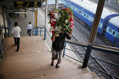 An Indian man carries a bundle of flowers to sell on the occasion of Christmas at Dadar Railway Station in Mumbai, India, Wednesday, Dec. 25, 2013. Although Christians comprise only two percent of the population among a Hindu majority, the holiday is observed across the country as an occasion to celebrate. (AP Photo/Rajesh Kumar Singh)