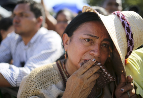 A woman cries during the funeral Mass for singer and composer Diomedes Diaz at the main square of Valledupar, Colombia's northern state of Cesar, Wednesday, Dec. 25, 2013. Diaz, one of the greatest performers of Colombia's accordion vallenato music, died Sunday, Dec. 22, 2013, at age 56. (AP Photo/Ricardo Mazalan)
