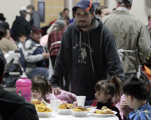 Leah Hogsten  |  The Salt Lake Tribune Carlos Delgado smiles as his children l-r Celina, 2, Daniel, 5 and Agolina,4, are fed a turkey and mashed potato dinner Wednesday, December 25th by the Salt Lake City Rescue Mission at The Christian Life Center.