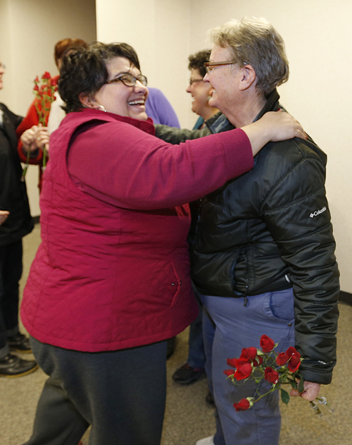 Jennifer Munson, left hands a flower to Arlene Arnold right outside the offices of the Utah County Clerk and Auditor office after Arlene received a rejection letter for a marriage license on Dec. 20, 2013 in Provo, Utah. Munson decided on her own to come down and bond out flowers after hearing the news. A Federal Judge on Friday struck down Utah's ban on same sex marriage saying the law violates the U.S. Constitution.  (Photo by George Frey  |  Special to the Tribune)