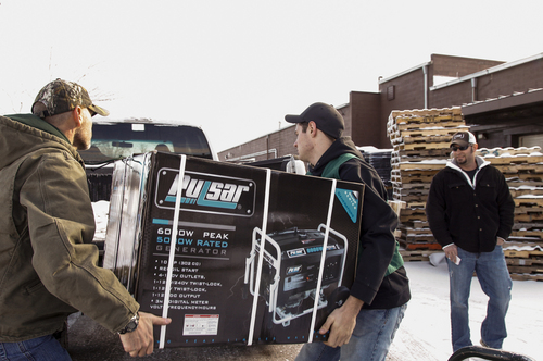 Family Farm & Home of Mason employees  and Dean Haynes,  left, and Bobby Hollon load a generator into Nathan Timm's truck, Tuesday, Dec. 24, 2013. Timm, of Ovid, was buying the generator for his parents, who live in Barry County and are without electricity. (AP Photo/Lansing State Journal, Matthew Dae Smith)