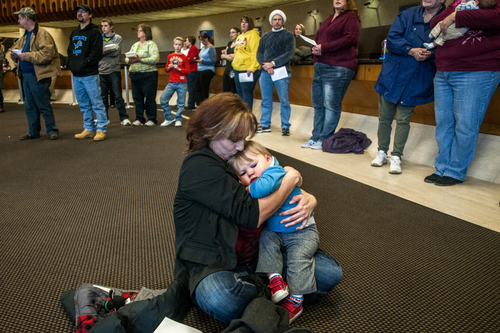 """Carla Coulter, 46, of Clio, holds her 1-year-old grandson Connor Hergert closely as she gives him a kiss on the forehead while listening to the FirstMerit Bank Mixed Chorus sing """"Silent Night"""" along with about 100 spectators during the 76th Annual Holiday Sing on Tuesday, Dec. 24, 2013 at FirstMerit Bank in downtown Flint, Mich. """"We don't have power. We're warming up, and I just feel so very blessed to have my family,"""" Coulter said. """"I don't need anything else."""" (AP Photo/The Flint Journal, Jake May)"""