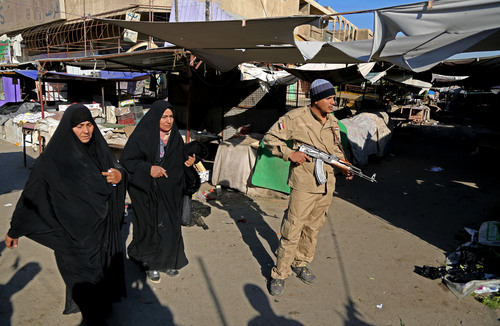 Karim Kadim  |  The Associated Press An awakening council member stands guard while women walk through the site of a bombing in a Christian section of Baghdad, Iraq, on Wednesday. Militants in Iraq targeted Christians in two separate bomb attacks in Baghdad, officials said. The Christmas Day attacks brought the total number of people killed so far this month in Iraq to 441. According to U.N. estimates, more than 8,000 people have been killed since the start of the year.