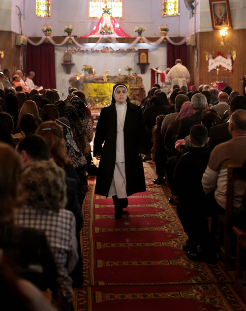 A nun walks as worshipers attend a Christmas mass at the Mother Teresa Catholic Church in Basra, Iraq's second-largest city, 340 miles (550 kilometers) southeast of Baghdad, Iraq, Wednesday, Dec. 25, 2013. Iraqi officials say a car bomb went off near a Baghdad church during Christmas Mass, more than a dozen people. (AP Photo/Nabil al-Jurani)