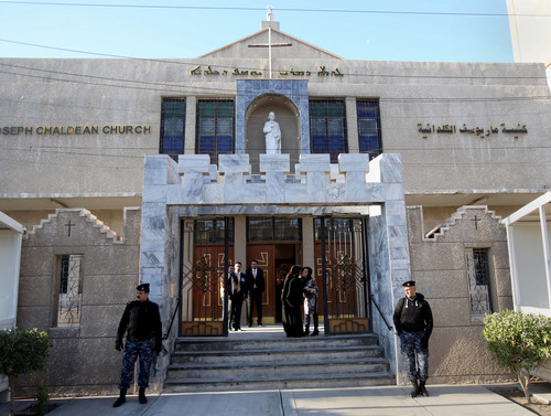 Iraqi police officers guard the entrance of St. Joseph's Chaldean Church before a Christmas mass in Baghdad, Iraq, Wednesday, Dec. 25, 2013. Militants on Wednesday launched two separate attacks against Christians in Baghdad, officials said. There was no immediate claim of responsibility for the attacks, but Iraq's dwindling Christian community, which is estimated to number about 400,000 to 600,000 people, has often been targeted by al-Qaida and other insurgents who see the Christians as unbelievers.(AP Photo/Karim Kadim)