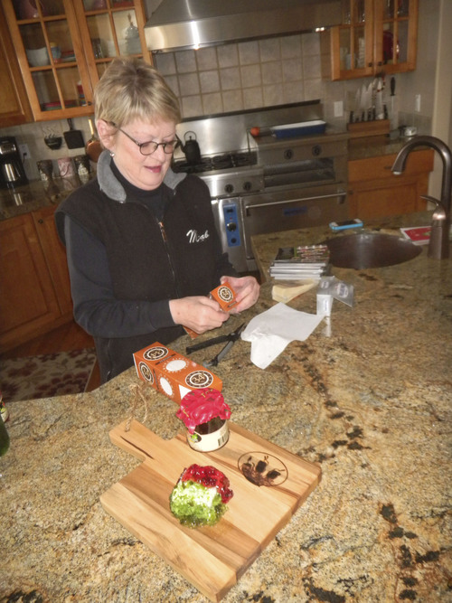 Pepperlane founder Michele Trover prepares some snacks using her pepper jelly preserves at her Wanship home. (Tom Wharton Photo)