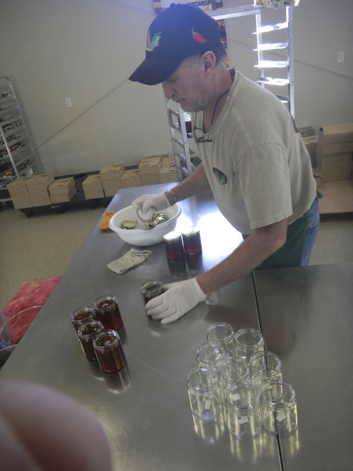 Pepperlane co-owner Rod Weese puts caps on bottles of the company's signature pepper jellies at Wanship plant. (Tom Wharton Photo)