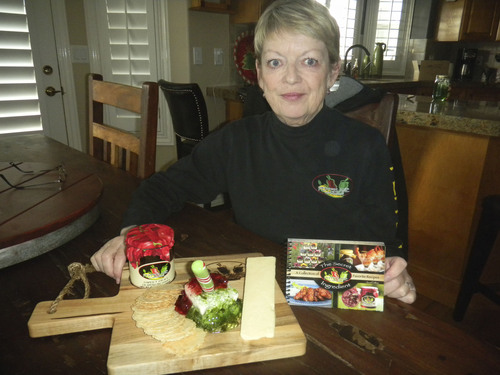 Michele Trover, founder of Pepperlane, shows off cookbook with recipes to use her company's 14 jelly preserves, most of which taste great with crackers or cheese. (Tom Wharton Photo)