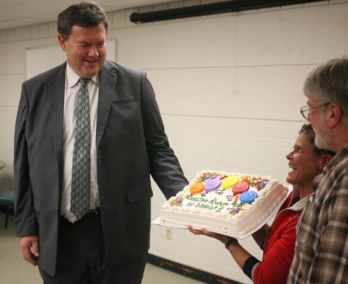 Lennie Mahler  |  The Salt Lake Tribune Carlton Christensen, District 1 Representative in the Salt Lake City Council, is presented with a cake by Gina Zivkovic and Steve Johnson in a meeting with the Fairpark Community Council at the Northwest Community Center on Thursday, Dec. 5, 2013. Christensen is leaving the council after serving for 16 years.