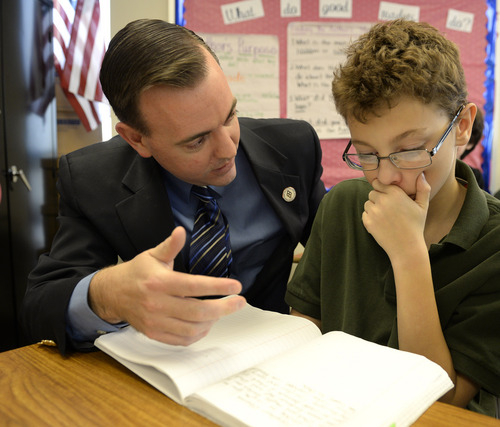 Rick Egan  | The Salt Lake Tribune   West Valley City Mayor Mike Winder helps Carson Hoffman, a sixth-grader at Endeavor Hall Charter School, write a letter asking President Obama to visit Utah, Thursday, Dec. 5, 2013.