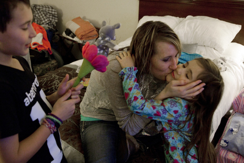 "Jill Ghantous, center, kisses her daughter, Briana Ghantous, 6, at the Wingate Hotel, on Wednesday, Dec. 25, 2013, in Grand Blanc Township, Mich. The Ghantous family lost power on Sunday at their home in Swartz Creek due to ice storms that have left about 40,000 people in Genesee County without power. Lacking power at their home, the family opened their Christmas presents Wednesday morning at the hotel. ""We had to put a sign in the window to let Santa know to come here,"" Jill Ghantous said. (AP Photo/The Flint Journal-MLive.com, Michelle Tessier) LOCAL TV OUT; LOCAL INTERNET OUT"