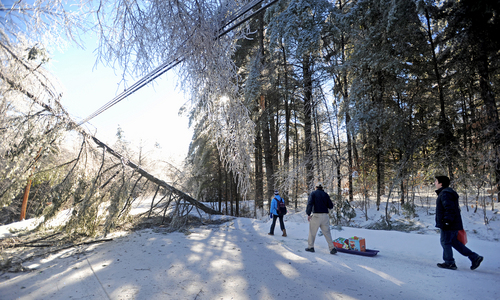 Chris Devine, center, hauls a sled of gifts with his daughter Jordan, 11, left, and stepson Derek Gervais, 20, right, to their home on Maplehurst Lane in Belgrade, Maine on Wednesday, Dec. 25, 2013. The Devine's lost power on Monday and have hauled their supplies in on sled ever since. Trees and power lines are down on both sides of their driveway, luckily they weren't home when the trees fell affording them the opportunity to drive to town for gas and other essentials for life off the grid. Central Maine Power says it could be at least a week before power is restored in rural areas like Belgrade. (AP Photo/Morning Sentinel, Michael G. Seamans)