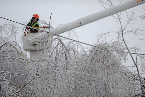 Andrew Powers, an arborist with Asplundh Tree Experts, clears iced branches from power lines along Mayflower Heights Drive in Waterville, Maine, on Monday, Dec. 23, 2013. Central Maine Power said nearly 57,000 were without power Monday afternoon, up from 29,000 it had been reporting earlier. Hardest hit was Kennebec County with about 20,000 and Waldo County at nearly 15,000 customers without power.  (AP Photo/Morning Sentinel, Michael G. Seamans)