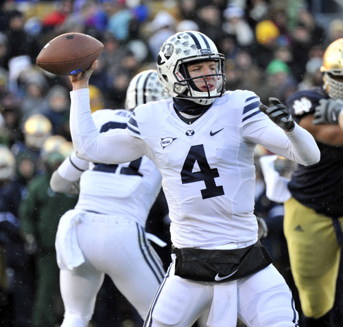 Brigham Young quarterback Taysom Hill throws a pass in the first half of an NCAA college football game Saturday, Nov. 23, 2013, in South Bend, Ind. (AP Photo/Joe Raymond)