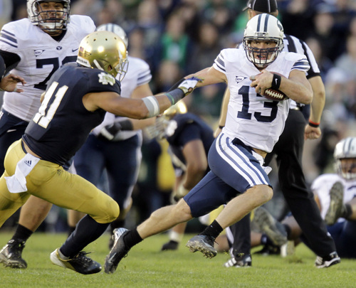BYU quarterback Riley Nelson, right, eludes Notre Dame linebacker Ishaq Williams during the second half of an NCAA college football game in South Bend, Ind., Saturday, Oct. 20, 2012. Notre Dame defeated BYU 17-14. (AP Photo/Michael Conroy)