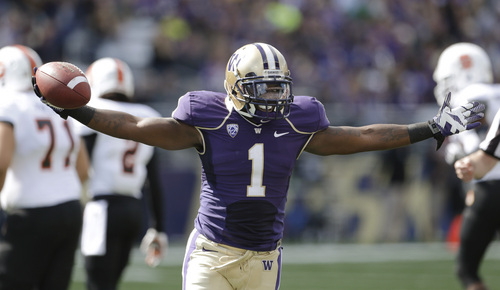 Washington safety Sean Parker raises his arms as he runs off the field after intercepting an Idaho State pass in the first half of an NCAA college football game Saturday, Sept. 21, 2013, in Seattle. (AP Photo/Elaine Thompson)