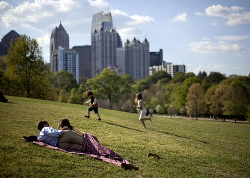 FILE - In this March 25, 2012, file photo, a couple enjoy a sunny afternoon against the backdrop of the Midtown skyline from Piedmont Park in Atlanta. A survey of human resource managers found they encouraged employees to take all their vacation time because it leads to more productive workers. (AP Photo/David Goldman, File)