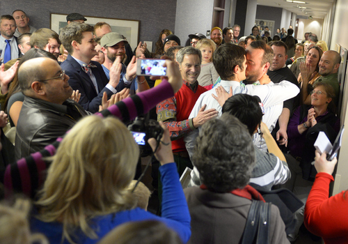 Keith Johnson | The Salt Lake Tribune  A crowd applauds outside the Salt Lake County clerks office, Friday, December 20, 2013 after Salt Lake Mayor Ralph Becker, center, performed the wedding for a gay couple who obtained a marriage license after a federal judge in Utah struck down the state's ban on same-sex marriage, saying the law violates the U.S. Constitution's guarantees of equal protection and due process. Hundreds flocked to obtain licenses .