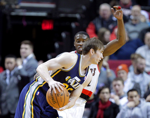 Utah Jazz guard Gordon Hayward, left, drives against Portland Trail Blazers guard Wesley Matthews during the first half of an NBA basketball game in Portland, Ore., Friday, Dec. 6, 2013. (AP Photo/Don Ryan)