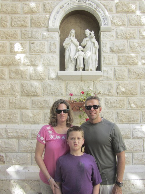 Courtesy of Eric Huntsman Eric and Elaine Huntsman, with their son, Samuel, in front of Holy Family statue in Israel.