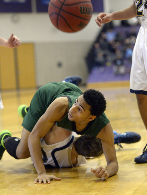 Francisco Kjolseth  |  The Salt Lake Tribune Mychell Halley of Kearns ends up on top of Zack Bourdreaux of Skyline during game action in the Riverton Holiday Tourney at Riverton High school on Friday, Dec. 27, 2013.