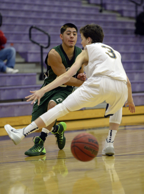Francisco Kjolseth  |  The Salt Lake Tribune Alex Zepeda manages a pass through the legs of Alex Meldrum of Skyline in the Riverton Holiday Tourney at Riverton High school on Friday, Dec. 27, 2013.