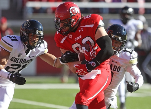 Utah tight end Jake Murphy (82) carries the ball for a touchdown as Colorado defensive back Jered Bell (21) and teammate defensive back Parker Orms (13) defend in the first quarter during an NCAA college football game Saturday, Nov. 30, 2013, in Salt Lake City. (AP Photo/Rick Bowmer)