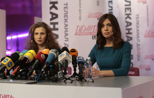 Russian punk band Pussy Riot members Nadezhda Tolokonnikova, right, and Maria Alekhina listen to questions during their news conference in Moscow, Russia, Friday, Dec. 27, 2013.Tolokonnikova and Alekhina were granted amnesty on Monday, Dec. 23, two months short of their scheduled release after spending nearly two years in prison for their protest at Moscow's main cathedral. (AP Photo/Ivan Sekretarev)