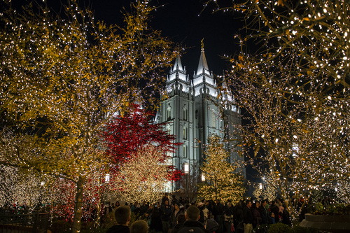 Chris Detrick  |  The Salt Lake Tribune Visitors look at the Christmas lights on Temple Square Friday November 29, 2013.  The first year the light were put up on Temple Square was in 1965. The lights will run through the end of the year.