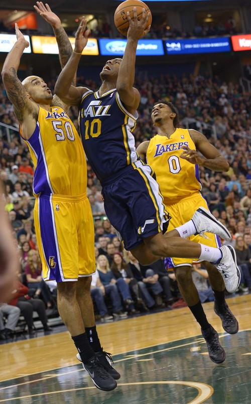 Leah Hogsten  |  The Salt Lake Tribune Utah Jazz point guard Alec Burks (10) drives aroundLos Angeles Lakers center Robert Sacre (50). The Utah Jazz defeated the LA Lakers 105-103, Friday, December 27, 2013 at Energy Solutions Arena in Salt Lake City.