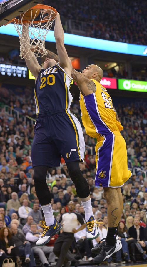 Leah Hogsten  |  The Salt Lake Tribune Utah Jazz shooting guard Gordon Hayward (20) dunks and is fouled by Los Angeles Lakers center Robert Sacre (50). The Utah Jazz defeated the LA Lakers 105-103, Friday, December 27, 2013 at Energy Solutions Arena in Salt Lake City.