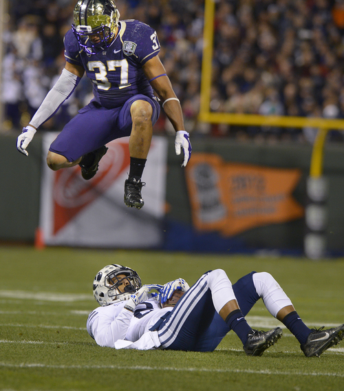 Scott Sommerdorf   |  The Salt Lake Tribune Washington Huskies linebacker Princeton Fuimaono (37) leaps over Brigham Young Cougars wide receiver Cody Hoffman (2) during first half play at the Fight Hunger Bowl at AT&T Park in San Francisco, Friday December 27, 2013.
