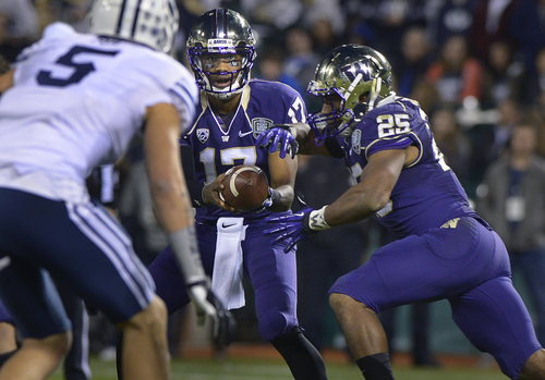 Scott Sommerdorf   |  The Salt Lake Tribune Washington Huskies quarterback Keith Price (17) reads Brigham Young Cougars linebacker Alani Fua (5) as he hands off to Washington Huskies running back Bishop Sankey (25) during first half play at the Fight Hunger Bowl at AT&T Park in San Francisco, Friday December 27, 2013.