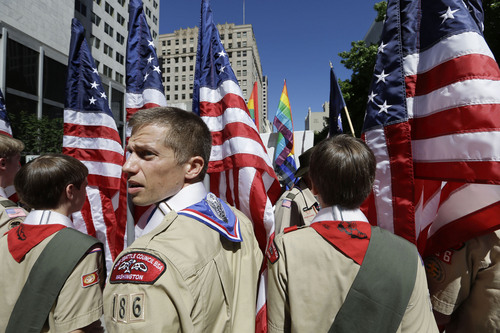 ADVANCE FOR USE SUNDAY, DEC. 29, 2013 AND THEREAFTER - FILE - In this June 30, 2013 file photo, Boy Scouts from the Chief Seattle Council carry U.S. flags as they prepare to march in the Gay Pride Parade in downtown Seattle. The Boy Scouts of America, in the most contentious change of membership policy in a 103-year history, will accept openly gay youths in Scout units starting on New Year's Day 2014. (AP Photo/Elaine Thompson, File)