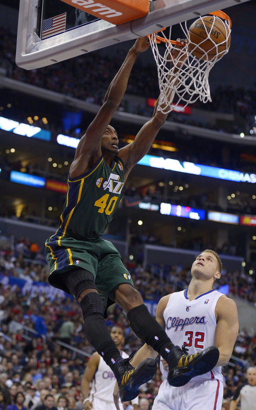 Utah Jazz forward Jeremy Evans, left, dunks as Los Angeles Clippers forward Blake Griffin looks on during the first half of an NBA basketball game, Saturday, Dec. 28, 2013, in Los Angeles. (AP Photo/Mark J. Terrill)