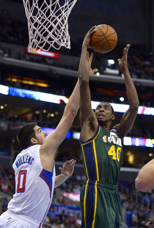 Utah Jazz forward Jeremy Evans, right, puts up a shot as Los Angeles Clippers center Byron Mullens defends during the first half of an NBA basketball game, Saturday, Dec. 28, 2013, in Los Angeles. (AP Photo/Mark J. Terrill)