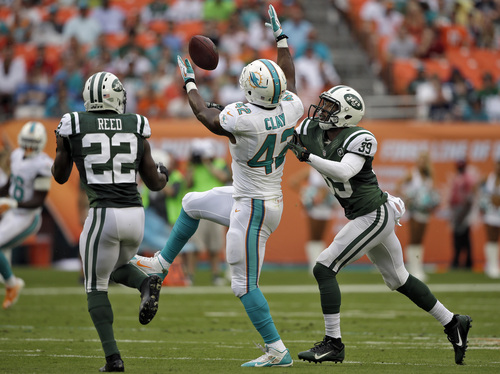 Miami Dolphins tight end Charles Clay (42) can't hang onto a pass from quarterback Ryan Tannehill as New York Jets defenders Ed Reed (22) and Antonio Allen (39) close in during the first quarter of an NFL football game Sunday, Dec. 29, 2013, in Miami Gardens, Fla. (AP Photo/Lynne Sladky)